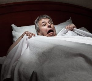 man wakes up from sleep with sleep paralysis scared and confused