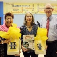 Source: The Leader News, Harvard Elementary Principal Kevin Beringer with Raiza Jan (left) and Elizabeth Suneby (center)